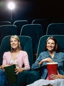Two young women watching movie in a movie theatre